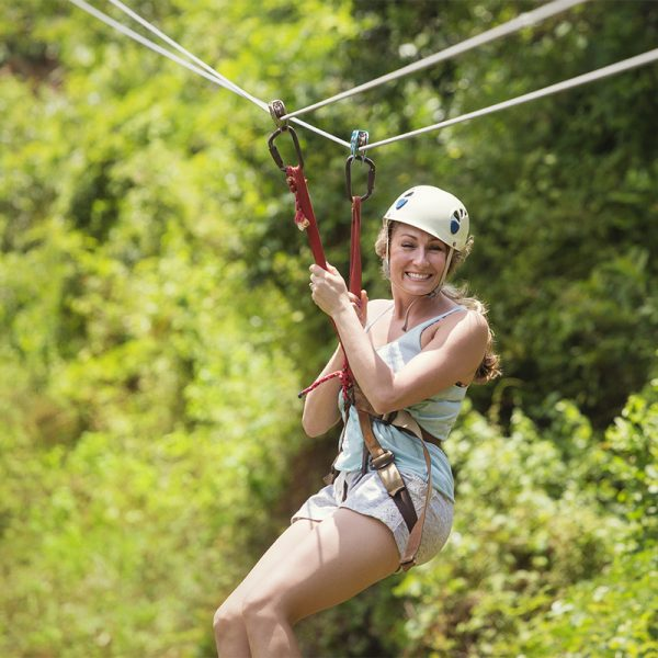 Woman glides across jungle canopy on Zip Line Canopy Tour