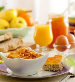 Healthy breakfast of whole grain cereal, eggs, fruit and juice.