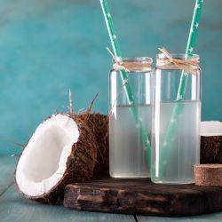 Delicious coconut water beside half a coconut.
